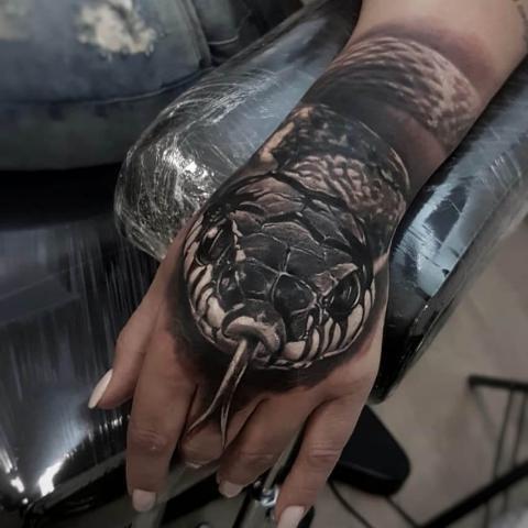 Damski tatuaż na dłoni wąż