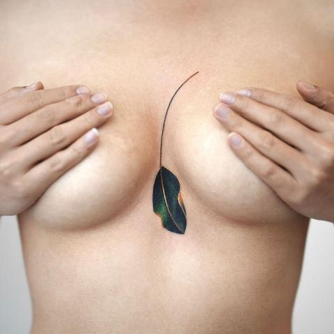 Kolorowy liść tatuaż między piersiami