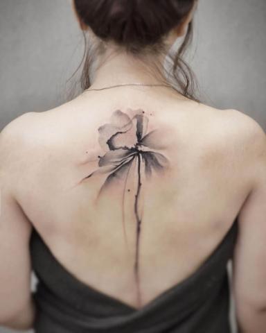 Kwiat na kręgosłupie tatuaże