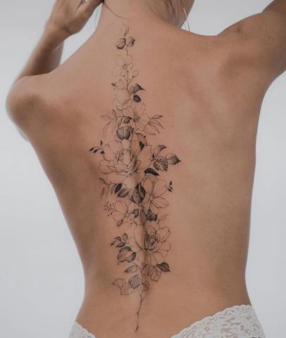 Kwiaty wzdłuż kręgosłupa tatuaż damski