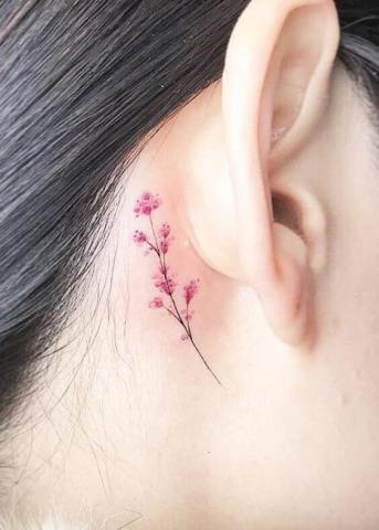 Minimalistyczny tatuaż kwiatek za uchem