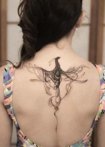Paw tatuaż na plecach u kobiety