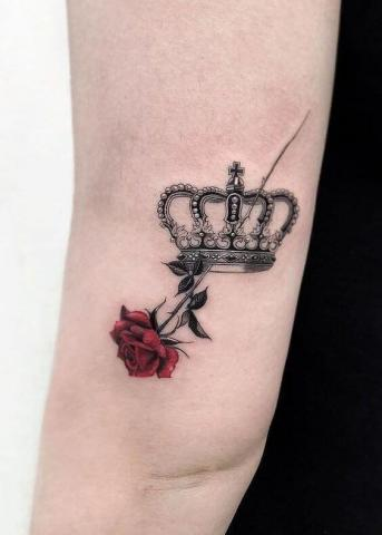 Tatuaż korona i róża na łokciu