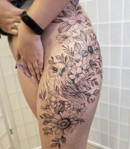 Tatuaż kwiaty i sowa na udzie