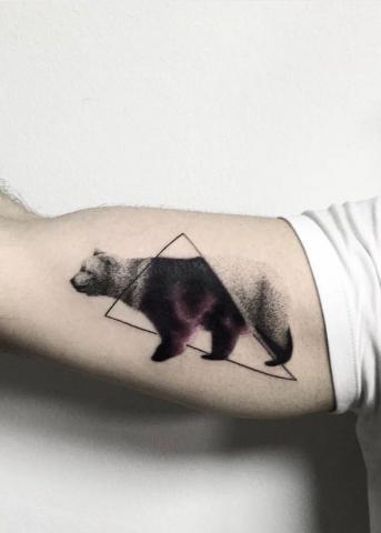 Tatuaż na bicepsie niedzwiedź