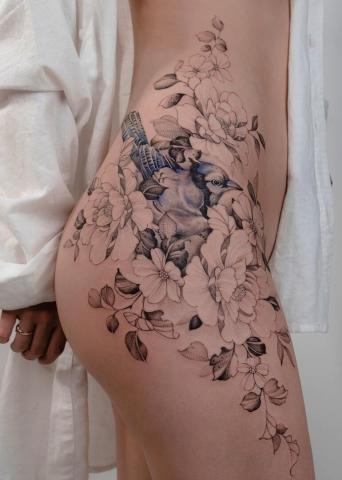 Tatuaże kobiece ptak i kwiaty