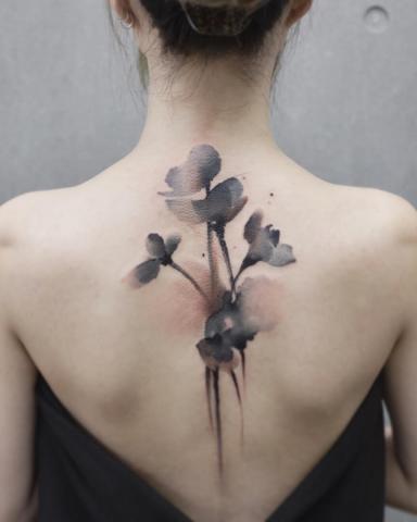 Tatuaże wzdłuż kręgosłupa damskie kwiaty