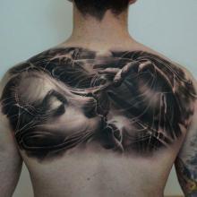 Męski tatuaż plecy kobieca twarz