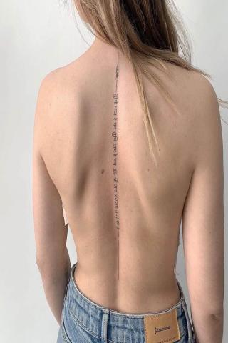 Damski tatuaż napis wzdłuż kręgosłupa