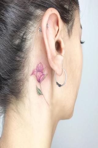Kwiatek za uchem tatuaż damski