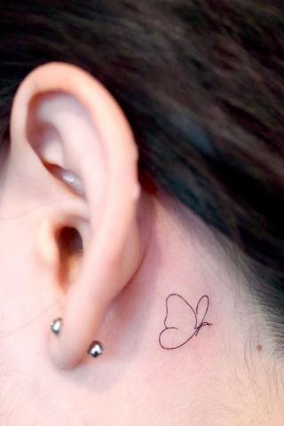 Tatuaż minimalistyczny motyl za uchem damski