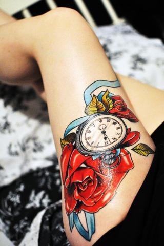 Zegar i kwiaty na udzie tatuaż